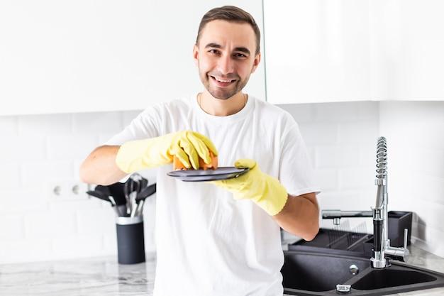 Homem bonito sorridente lavando louça na cozinha