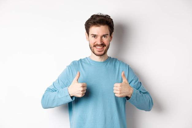 Homem bonito sorridente mostrando os polegares para cima, curtindo e aprovando a boa escolha, elogiando ou recomendando algo, em pé sobre fundo branco