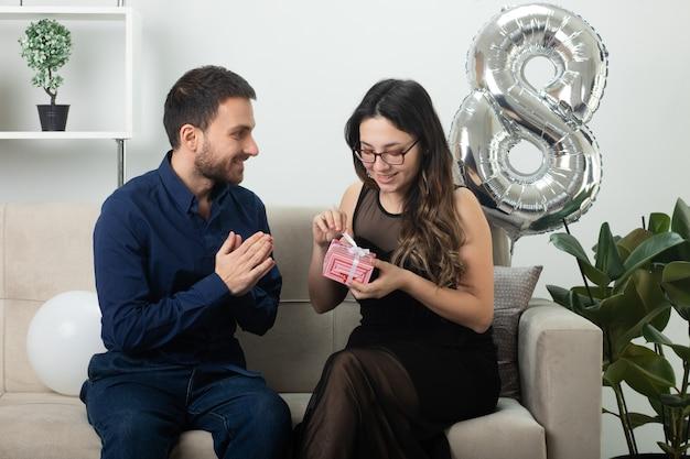 Homem bonito sorridente, olhando para uma bela jovem satisfeita em óculos ópticos abrindo uma caixa de presente, sentada no sofá na sala de estar, em março, dia internacional da mulher