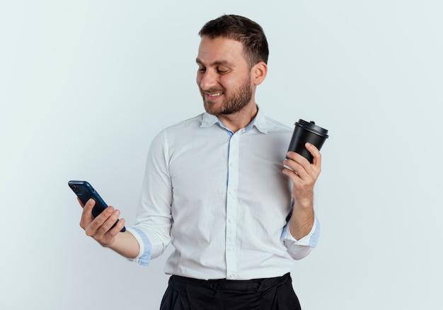 Homem bonito sorridente segura a xícara de café e olha para o telefone isolado na parede branca