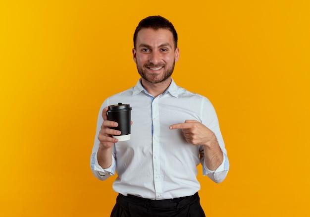 Homem bonito sorridente segura e aponta para a xícara de café isolada na parede laranja