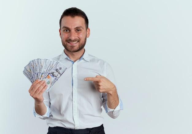 Homem bonito sorridente segura e aponta para dinheiro isolado na parede branca