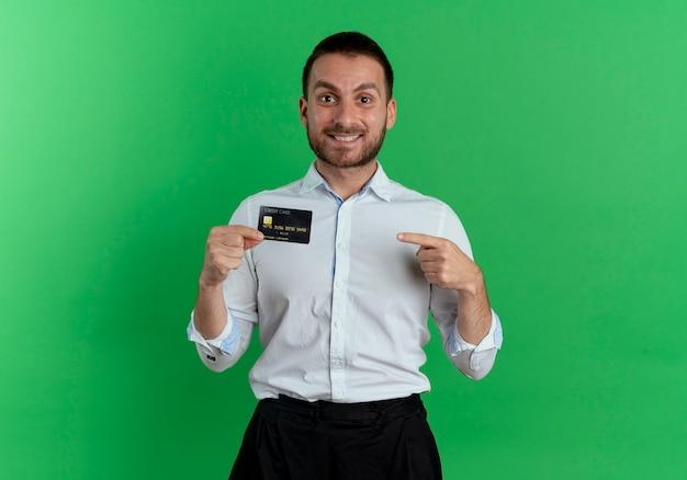 Homem bonito sorridente segura e aponta para o cartão de crédito isolado na parede verde