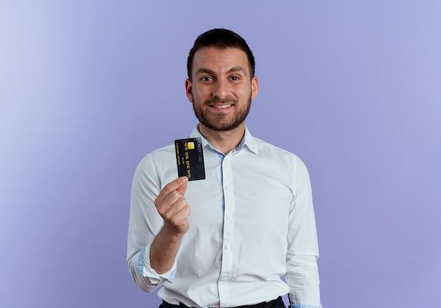 Homem bonito sorridente segurando cartão de crédito isolado na parede roxa