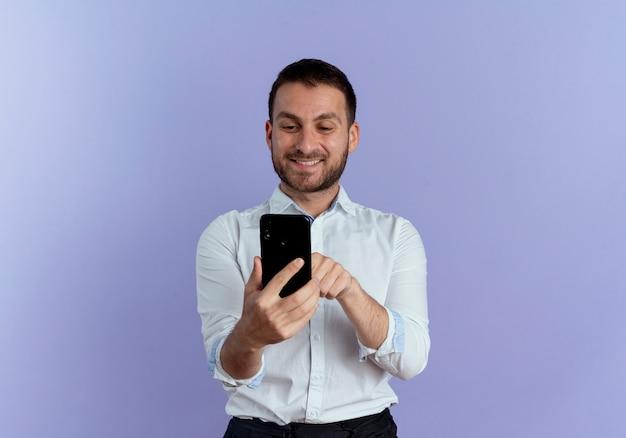 Homem bonito sorridente segurando e olhando para o telefone isolado na parede roxa