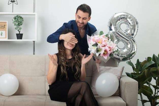 Homem bonito sorridente segurando um buquê de flores e fechando os olhos de uma bela jovem de óculos ópticos, sentada no sofá na sala de estar em março, dia internacional da mulher