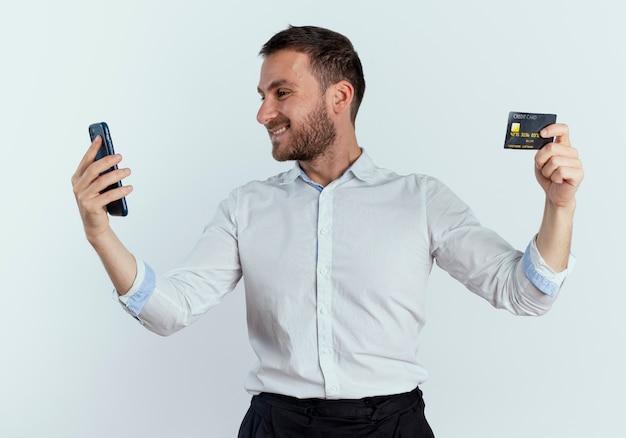 Homem bonito sorridente segurando um cartão de crédito e olhando para o telefone isolado na parede branca
