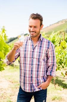 Homem bonito sorridente segurando um copo de vinho
