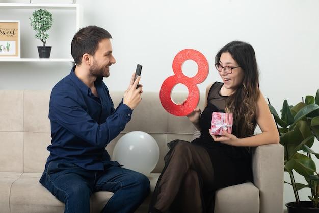 Homem bonito sorridente tirando foto de uma bela jovem alegre em óculos ópticos segurando uma caixa de presente e um número oito vermelho sentado no sofá na sala de estar em março, dia internacional da mulher