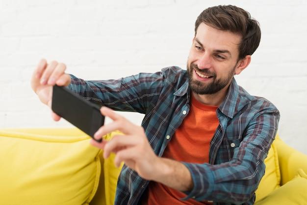 Homem bonito sorridente tomando uma selfie