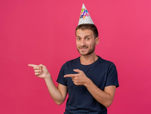 Homem bonito sorridente usando a tampa do aniversário apontando ao lado com as duas mãos isoladas na parede rosa com espaço de cópia