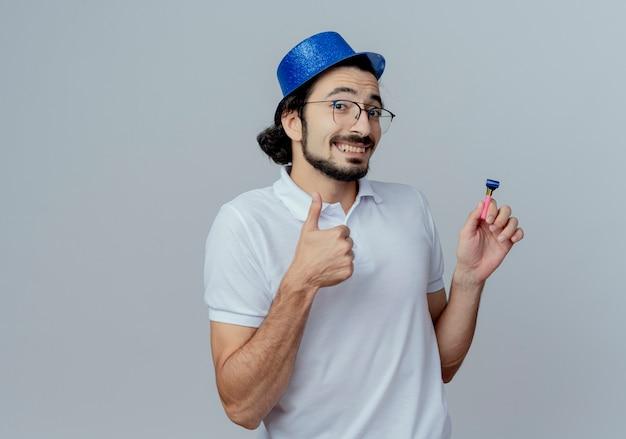 Homem bonito sorridente usando óculos e chapéu azul segurando o apito e o polegar isolado no branco