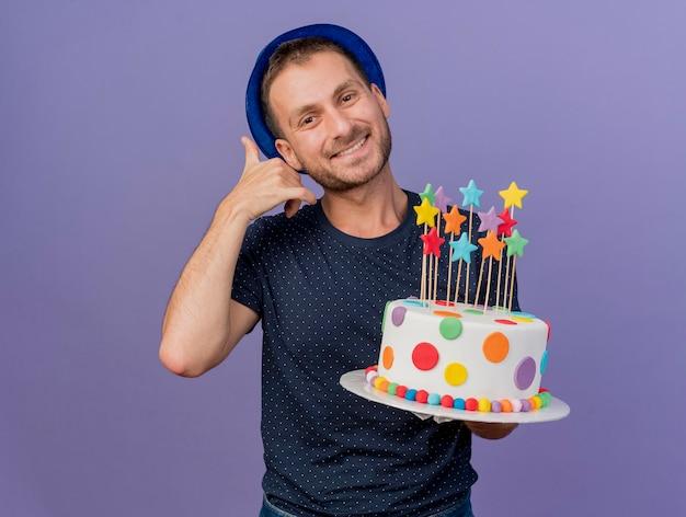 Homem bonito sorridente usando um chapéu azul, gestos me chama de sinal e segurando um bolo de aniversário isolado na parede roxa com espaço de cópia