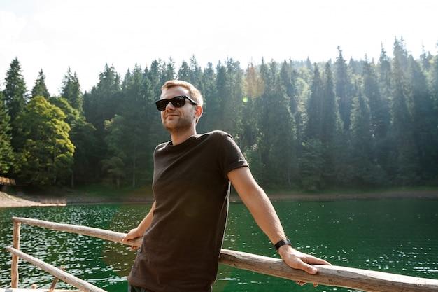 Homem bonito, sorrindo, apreciando a vista das montanhas, lago e floresta