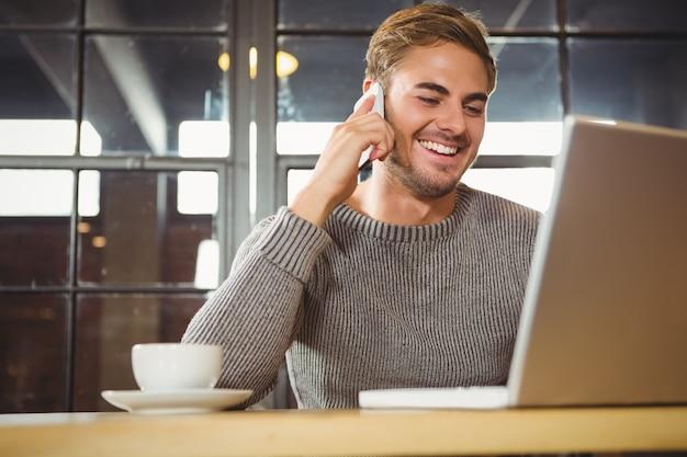 Homem bonito sorrindo e telefonando com smartphone