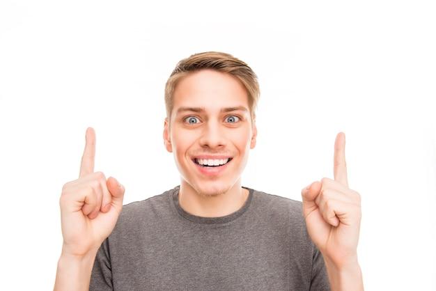 Homem bonito sorrindo, gesticulando com os dedos e apontando para cima