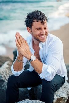 Homem bonito sorrindo na costa rochosa