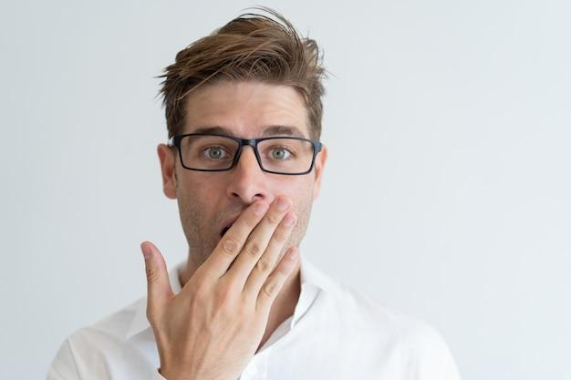 Homem bonito surpreso cobrindo a boca com a mão