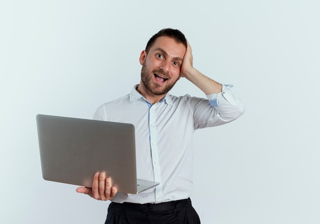 Homem bonito surpreso com a mão na cabeça segurando laptop isolado na parede branca