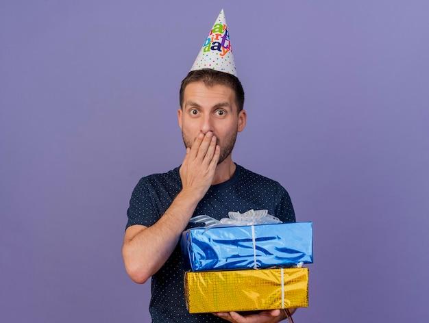 Homem bonito surpreso com boné de aniversário e colocando a mão na boca segurando caixas de presente isoladas na parede roxa com espaço de cópia