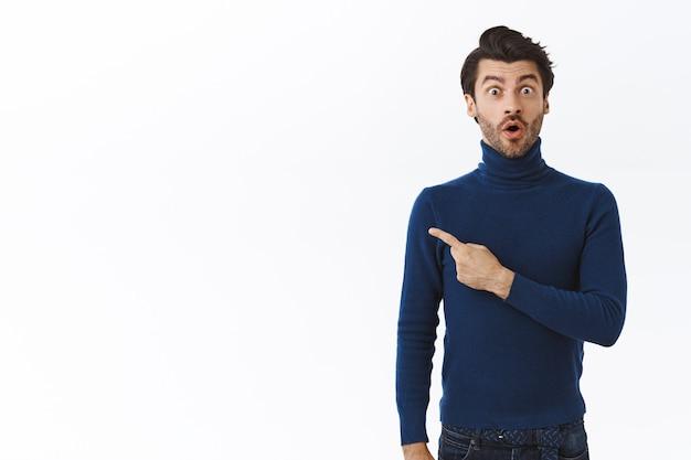 Homem bonito surpreso e impressionado com cerdas em um suéter azul de gola alta, percebe um evento interessante andando por aí, apontando para a esquerda, dobrando os lábios em uau, olhando a câmera atônita, parede branca