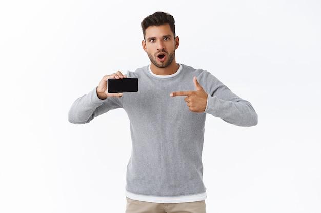 Homem bonito surpreso e oprimido de suéter cinza, fazendo perguntas sobre um jogo ou aplicativo para celular, segurando o smartphone horizontalmente, falando para a câmera, intrigado, apontando a tela
