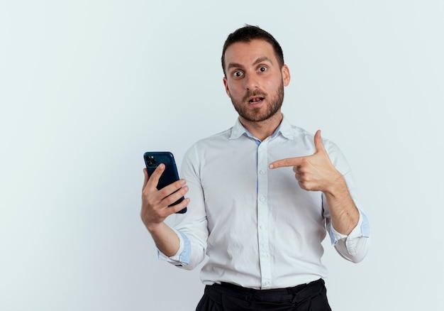 Homem bonito surpreso segurando e apontando para um telefone isolado na parede branca