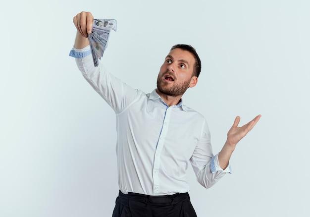 Homem bonito surpreso segurando e olhando para o dinheiro isolado na parede branca