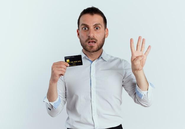 Homem bonito surpreso segurando um cartão de crédito e gesticulando quatro com a mão isolada na parede branca