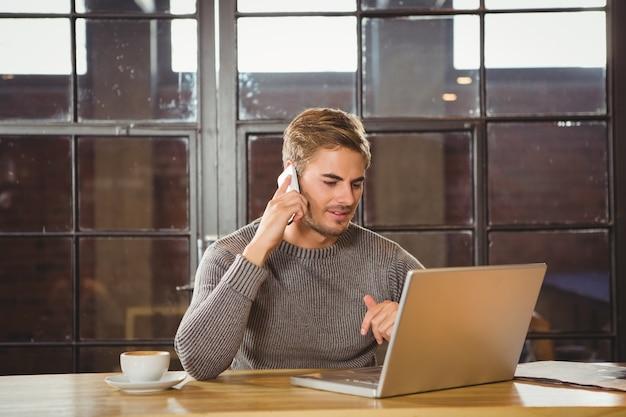 Homem bonito telefonando e olhando laptop