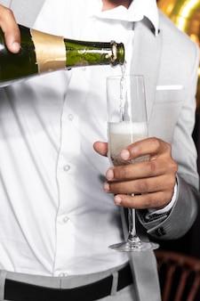 Homem bonito terno derramando champanhe em um copo
