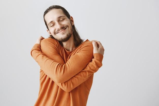 Homem bonito terno feliz fechando os olhos e se abraçando