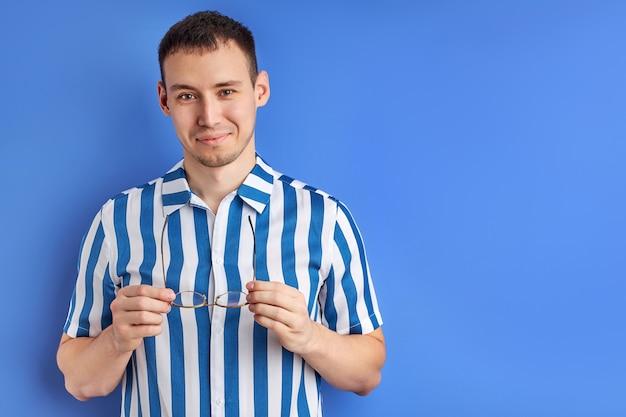 Homem bonito tirando os óculos e olhando para a câmera isolada no fundo azul, retrato