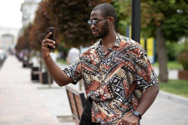 Homem bonito tirando selfie com smartphone moderno ao ar livre
