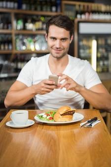 Homem bonito, tirando uma foto de sua comida