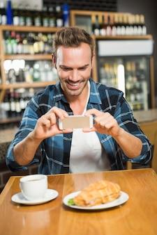 Homem bonito, tirando uma foto do seu sanduíche