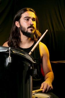 Homem bonito tocando bateria com varas