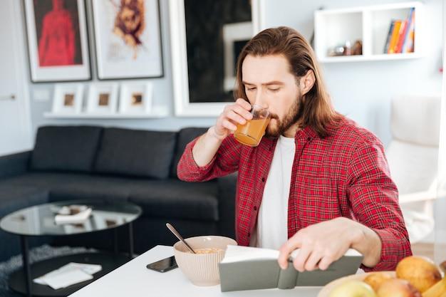 Homem bonito tomando café da manhã e lendo o livro em casa