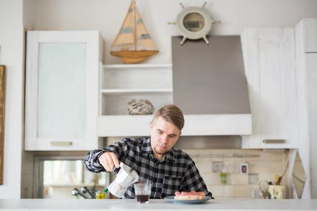 Homem bonito tomando café na cozinha