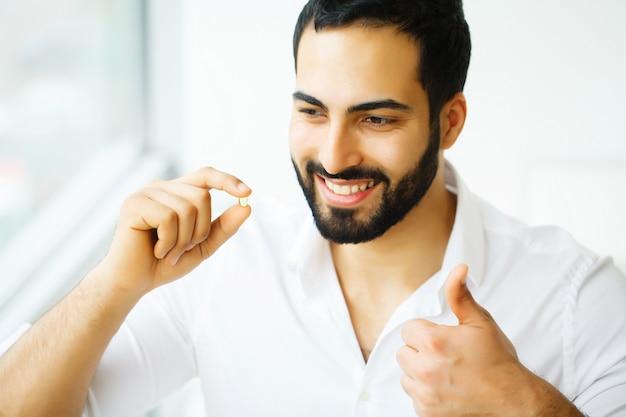 Homem bonito tomando pílula