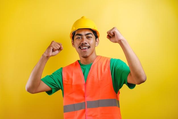 Homem bonito trabalhador asiático vestindo uniforme e capacete sobre fundo amarelo isolado, comemorando surpreso e espantado pelo sucesso com os braços erguidos e olhos abertos. conceito de vencedor.