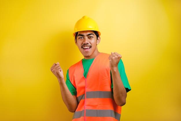 Homem bonito trabalhador asiático vestindo uniforme e capacete sobre fundo amarelo isolado, comemorando surpreso e espantado pelo sucesso com os braços levantados e olhos abertos. conceito de vencedor.