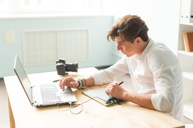 Homem bonito trabalhando com tablet gráfico