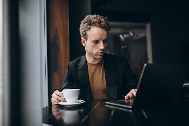Homem bonito, trabalhando em um computador em um café e beber café