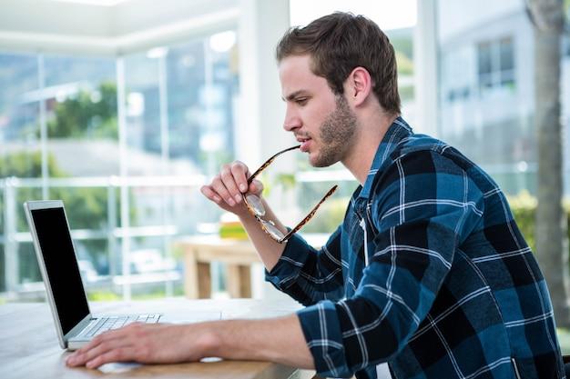 Homem bonito, trabalhando no laptop em um escritório brilhante