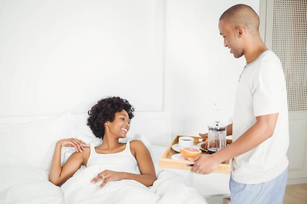 Homem bonito, trazendo café da manhã para sua namorada na cama