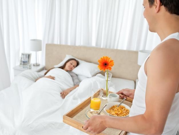 Homem bonito trazendo o café da manhã para sua namorada
