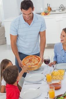 Homem bonito, trazendo uma pizza para sua família