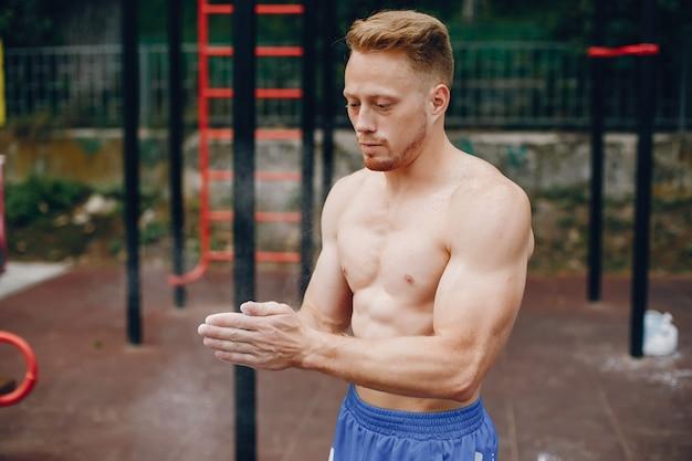 Homem bonito, treinando em um parque de verão