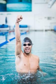 Homem bonito, triunfando com braços erguidos na piscina